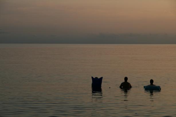 Ryan, Joseph i Ryan. Trzech amerykańskich surferów z Utah ogląda zachód słońca na Pacyfiku.